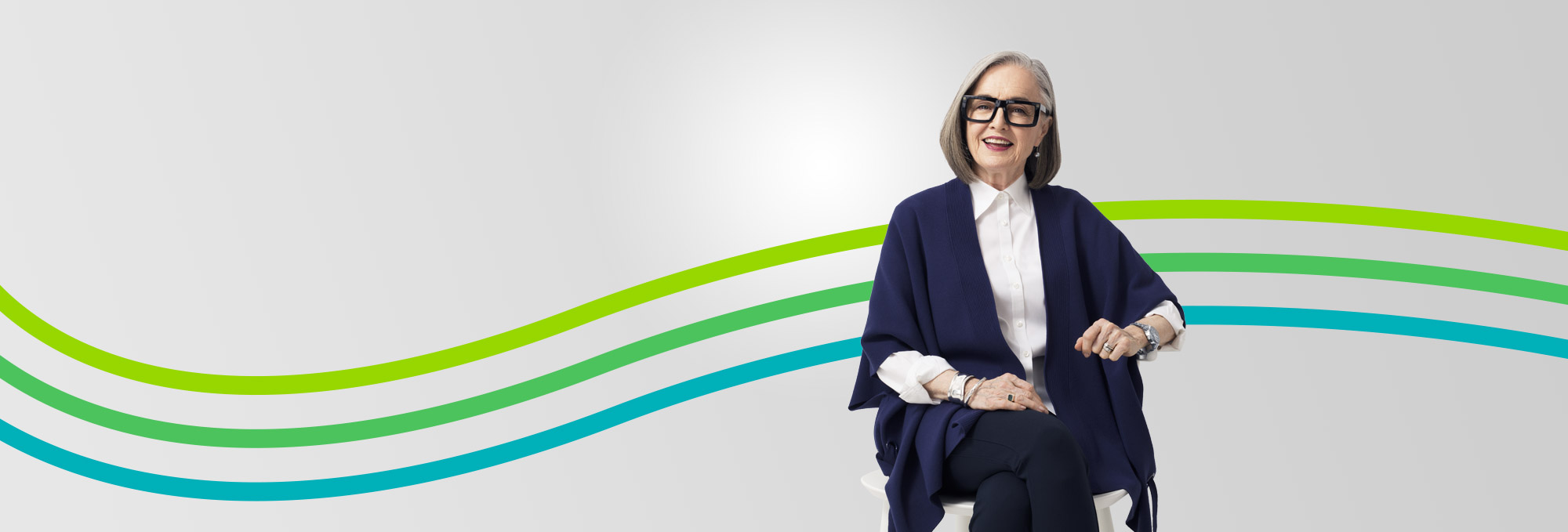 smiling retired woman in glasses featured in an article about revisiting your financial plan